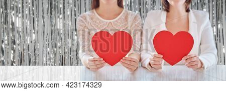 homosexuality, valentine's day and love concept - close up of happy lesbian couple holding red paper hearts over foil party curtain on background