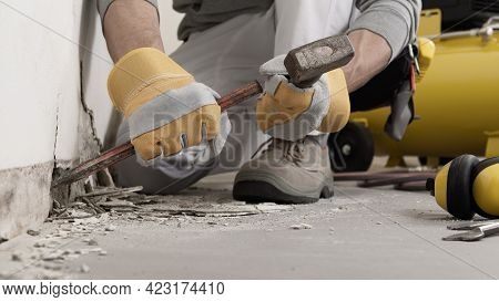 Construction Worker Hands With Gloves Working With Hammer And Chisel To Remove Old Plaster From Wall