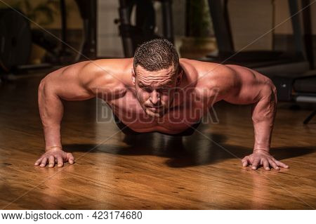 Muscular Man Doing Push-ups On One Hand Against Gym Background. Sport. Muscular And Strong Guy Exerc