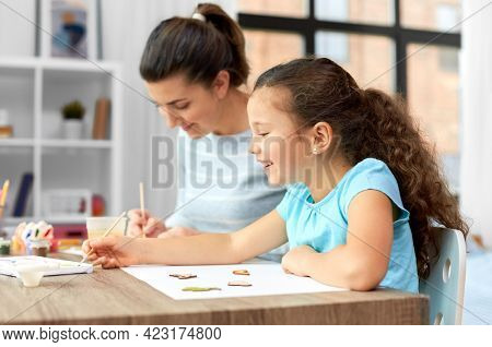 family, hobby and leisure concept - happy smiling mother spending time with her little daughter drawing or painting wooden chipboard cutouts with colors at home