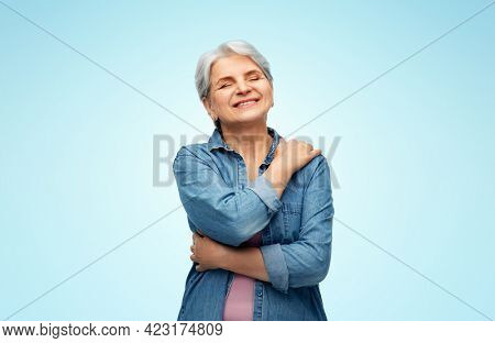 self-care, retirement and old people concept - portrait of smiling senior woman in denim shirt over blue background