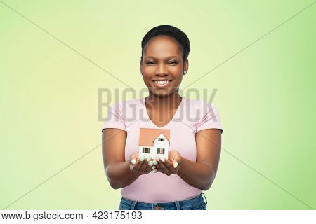 mortgage, real estate and accommodation concept - happy smiling african american woman holding house model over green background