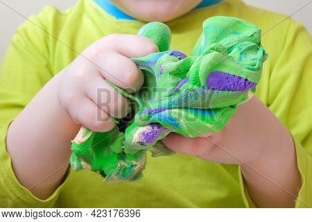 Lose-up Of Childrens Hands Gripping Soft Plasticine. The Concept Is The Development Of Creative Thin