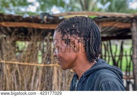 Profile of smiling African man with dreadlocks , portrait standing in his yard in a village in Botswana