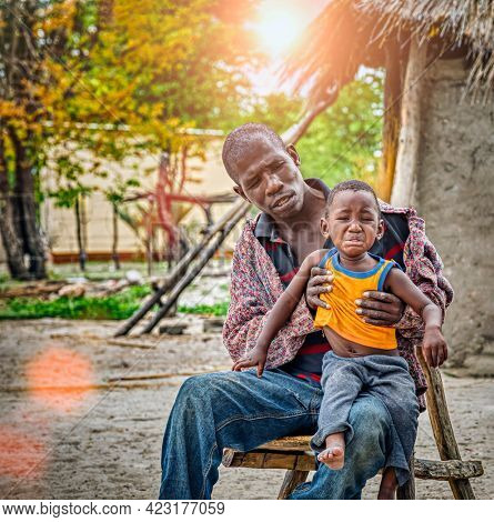 African family, father holding his child, yard in a village in Botswana