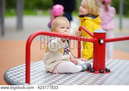 Toddler Girl Having Fun On Outdoor Playground. Preschooler Brother Rides Younger Sister On Carousel.