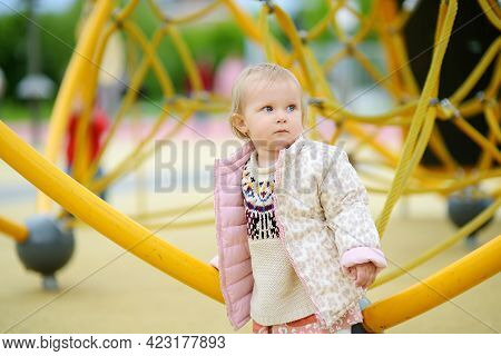 Cute Toddler Baby Having Fun On Outdoor Playground. Kindergarten, Daycare, Nursery For Small Childre