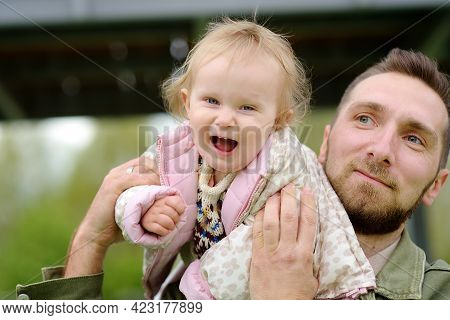 Cute Toddler Girl Having Fun On Outdoor Playground. Young Father Playing With Her Little Daughter. S