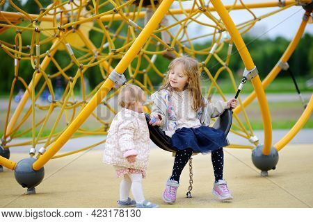 Two Cute Child Having Fun On Outdoor Playground. Spring/summer/autumn Active Sport Leisure For Kids.