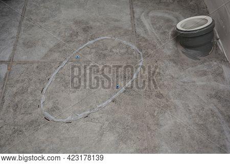 Toilet Bowl Installation On A Tiled Floor In A Bathroom. Applying A Glue On A Tiled Floor To Glue A