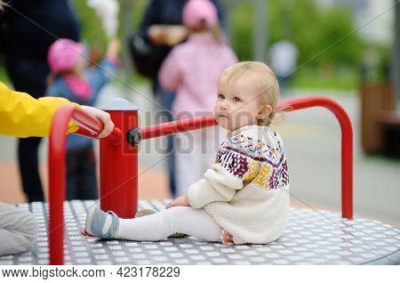 Cute Toddler Girl Having Fun On Outdoor Playground. Baby Rides On Carousel. Kindergarten, Daycare, N