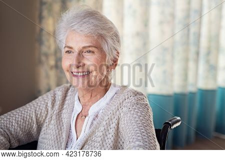 Happy old woman sitting on wheelchair and recovering from illness while looking through the window. Handicapped eldelry woman sitting in wheelchair with a positive expression towards the future.