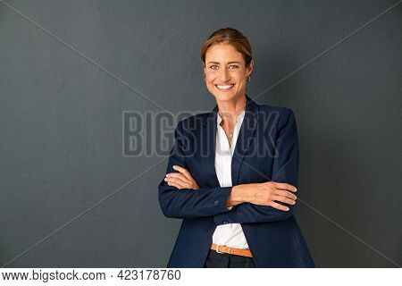 Confident mature woman with crossed arms in formal clothing with copy space looking at camera. Happy smiling mid adult woman standing against grey background. Portrait of beautiful businesswoman.