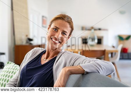 Happy mature woman relaxing on couch at home in living room. Close up face of middle aged woman looking at camera with copy space. Portrait of happy casual woman smiling and sitting on couch at home.