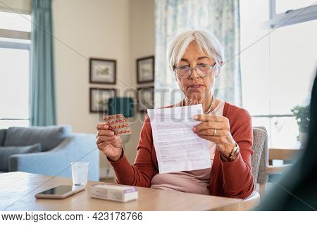 Senior woman checking prescription and dosage of medicine. Elderly lady reading medical instructions before taking medicine. Senior woman reading side effects list of drug and contraindications.