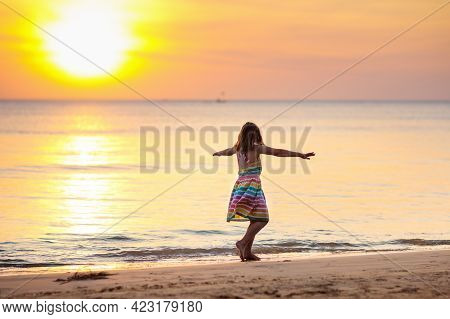 Child Playing On Ocean Beach. Kid At Sunset Sea.