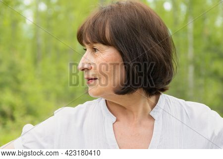 Portrait Of One Woman 60 Years Old In A Summer Forest. The Woman Is Depicted In Profile.