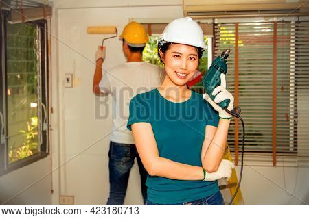 Happy Woman Asian Wearing A Safety Helmet Is Happy With Reno. Housework Holds An Electric Drill Read