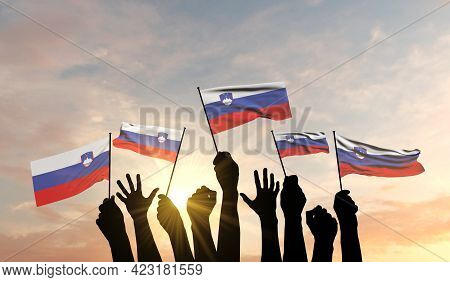 Silhouette Of Arms Raised Waving A Slovenia Flag With Pride. 3d Rendering