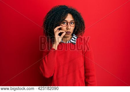 Beautiful african american woman with afro hair wearing sweater and glasses mouth and lips shut as zip with fingers. secret and silent, taboo talking