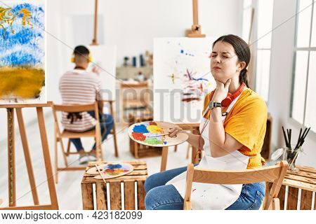 Young artist woman painting on canvas at art studio touching painful neck, sore throat for flu, clod and infection