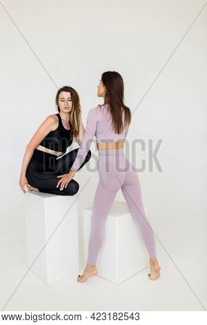 Two Sports Girls Posing Isolated On A White Background. Fitness Model Woman In Studio With Copy Spac