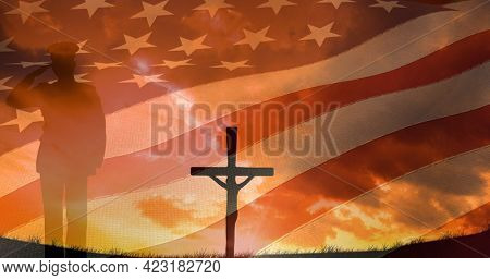 Composition of crucifix and soldier silhouette saluting over american flag. american patriotism and religion concept digitally generated image.
