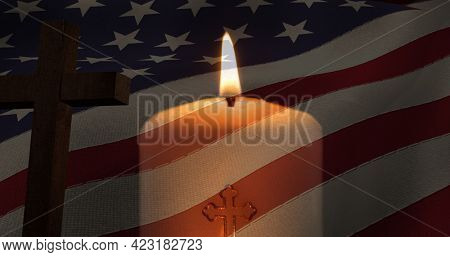 Composition of crucifix and candle over american flag. american patriotism and religion concept digitally generated image.