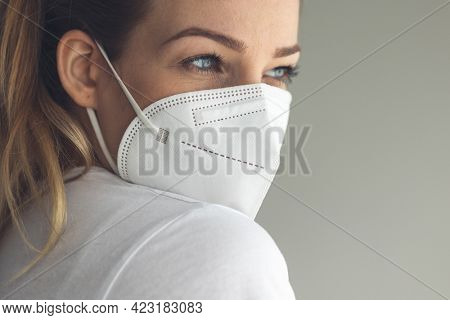 Young woman wearing a face mask during coronavirus and flu outbreak. Virus and illness protection, home quarantine. COVID-19 concept