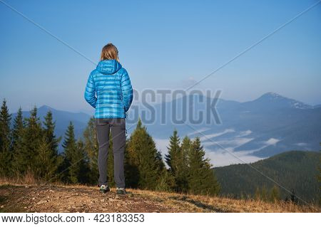 Rear View Of Female Traveler Standing On Top Of Mountain Hill And Looking At The Panorama Of Mountai
