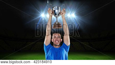 Portrait of caucasian male athlete lifting a trophy against floodlights in background. sports and fitness concept