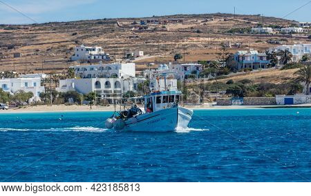 Fishing Boat Departing, Village Background. Koufonisi Island, Cyclades, Greece.