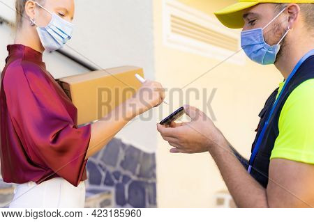Caucasian Woman With Protective Mask Appending Signature Sign On Smart Phone After Accepting Receive