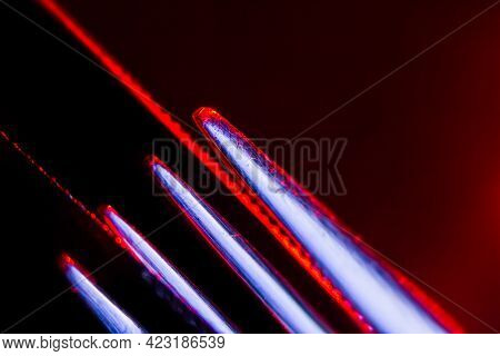 Edges Of Two Illuminated  Serrated Knives And Prongs Of A Fork Macro Shot. Image Suitable As A Backg