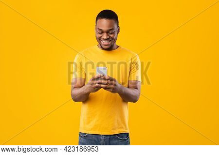 Smiling Black Man Using Smartphone Browsing Internet Over Yellow Background