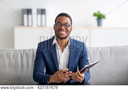 Portrait Of Happy Black Male Psychologist Looking At Camera And Taking Notes During Therapy Session