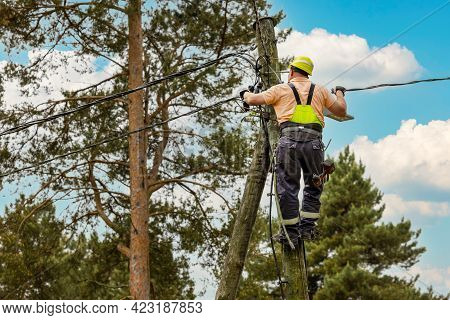 Electrical Lineman Connecting Wires High On Electric Pole. Powerline Maintenance And Repair