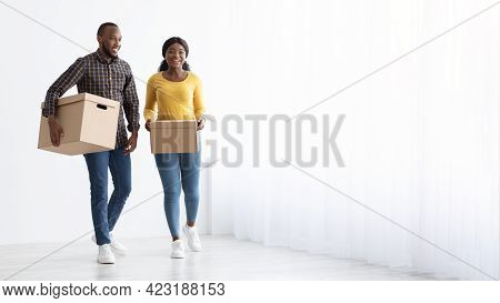 Relocation Concept. Young African American Spouses Walking With Cardboard Boxes Near Window