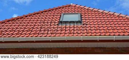Roofing Construction. A Red Tiled Roof With A Skylight Window Installed, A Plastic Rain Gutter, A Fa