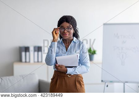 Professional Psychotherapy. Portrait Of Young Black Female Psychologist Holding Clipboard, Smiling A