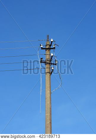 A Utility Pole, Electrical Post With Broken Power Lines, Damaged Electrical Cables After A Storm, Or