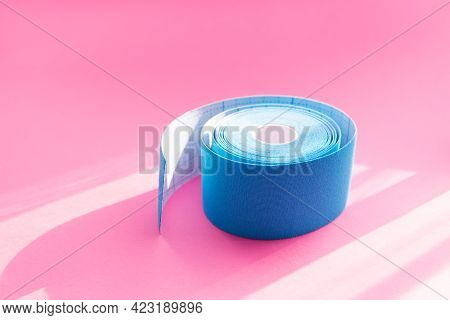 Close Up Blue Roll Of Kinesiology Tape On Pink Background With Trendy Sun Light And Shadows. Recover