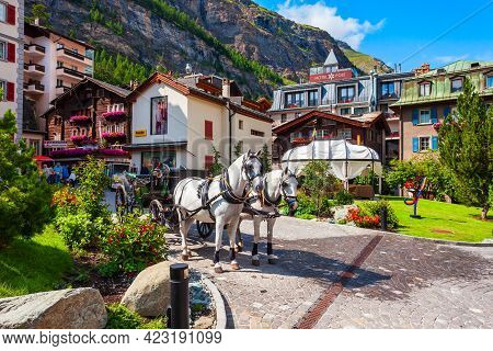 Zermatt, Switzerland - July 15, 2019: Horse Coach And Traditional Local Houses In The Centre Of Zerm