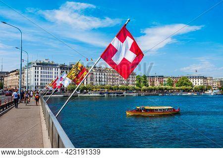 Geneva, Switzerland - July 20, 2019: Swiss Flags At The Pont Du Mont Blanc Bridge In Geneva City In