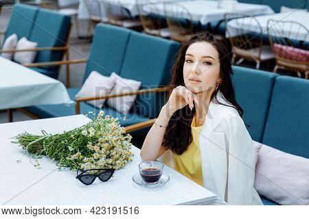 Close Up Portrait Of A Beautiful Caucasian Girl Sitting At Table In Summer Cafe In The Street. Woman