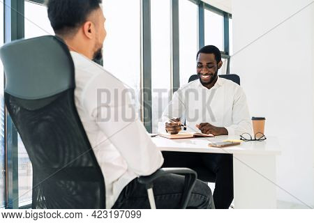 Two Multiracial Businessmen At Meeting In The Office