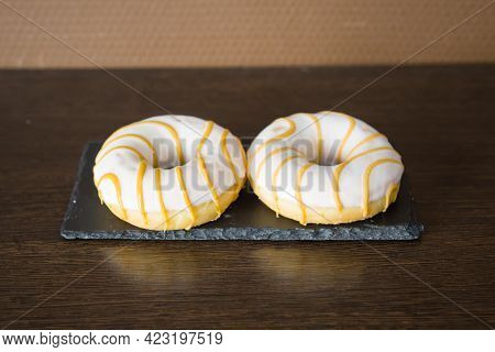 A Doughnut Ring Covered In White Chocolate And Yellow Caramel Stripes On A Brown Background. Confect