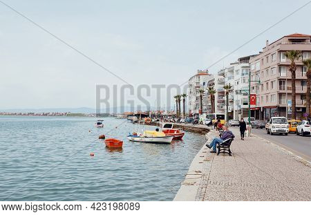 Ayvalik, Turkey: Sea Banks Past The Turkish Town With Moored Fishing Boats, And Buses On Town Road O