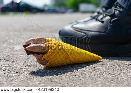 A Man Threw A Tasteless Chocolate Ice Cream In A Waffle Cone On The Asphalt Under His Feet, Taking A
