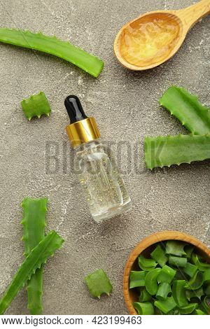 Aloe Vera Gel On Wooden Spoon With Aloe Vera And Oil Bottle On Grey Background. Top View.